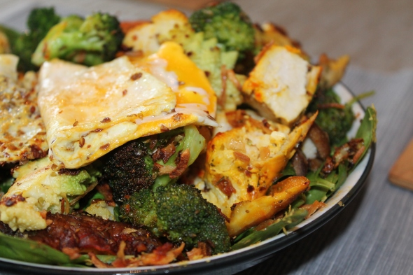 Spinach-Salad-Bed topped with saffron chicken breast, broccoli, cauliflower, shiitake and a folded sunny side up egg with flax