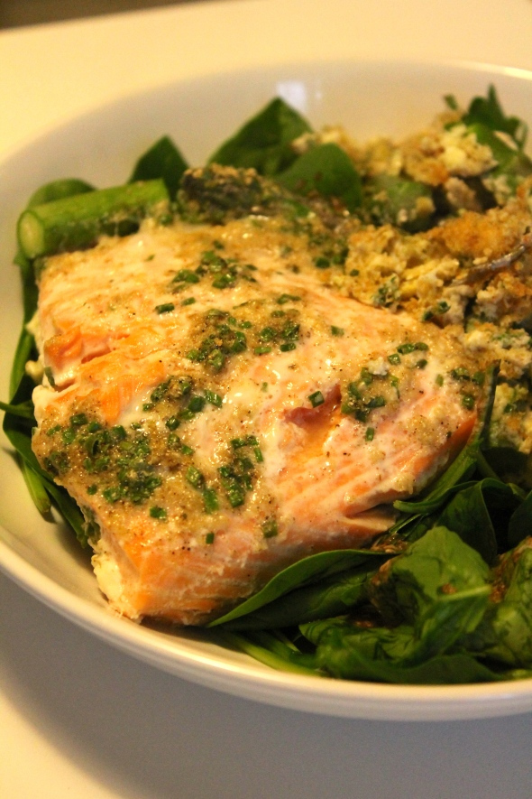 Salmon baked in eggs with asparagus on spinach salad